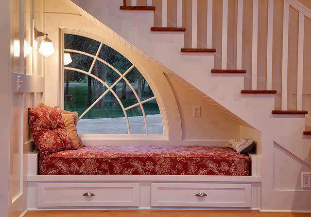 Una cama pequeña bajo la escalera